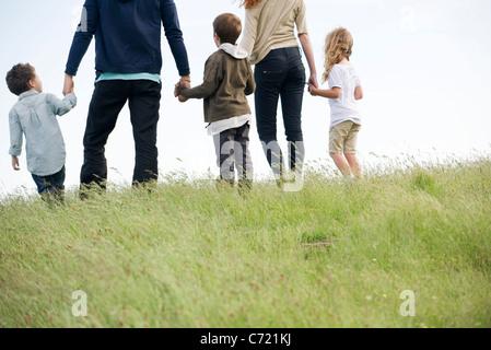 Familie gehen zusammen im Feld, Rückansicht - Stockfoto