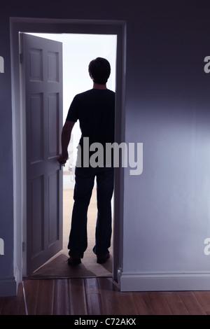 Rückansicht einer männlichen Figur in einem gut beleuchteten Raum verlassen eines dunklen Raumes - Stockfoto