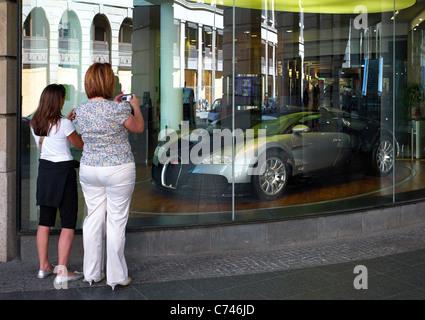 Zwei Frauen fotografieren einen Bugatti in einem Schaufenster Berlin Deutschland - Stockfoto