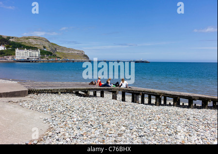 Junge Studentinnen Sonnenbaden auf einem hölzernen Steg an Llandudno Küste, Meer, Pier, great Orme mit blauem Himmel. - Stockfoto
