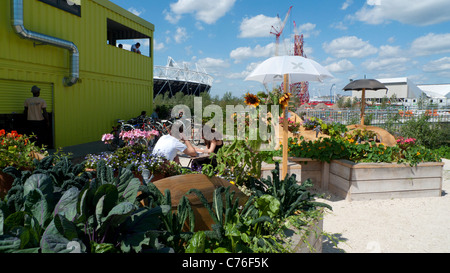 Ein paar sitzen im Freien Essen im Cafe im Blick Rohr Bereich mit Blick auf das Olympiastadion in Stratford, Newham - Stockfoto