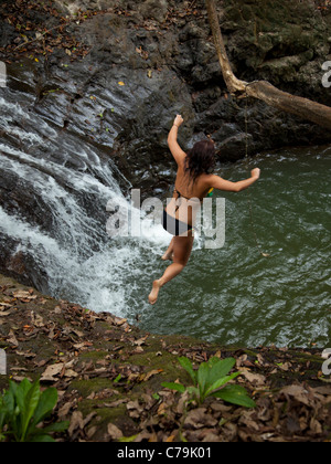 Costa Rica, junge Frau springt in Pool mit Wasserfall - Stockfoto