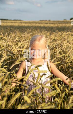 Mädchen, 6 Jahre alt, trägt ein Kleid in einem Weizenfeld im Sommer, Eyendorf, Niedersachsen, Deutschland, Europa