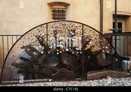 Metallgitter zum Schutz eines alten Wasserrad fällt in Vorhängeschlösser mit Nachrichten der ewigen Liebe und Hingabe, - Stockfoto