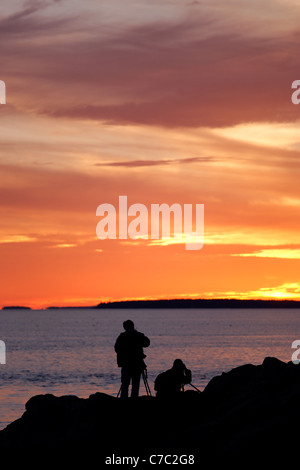 Zwei Fotografen fotografieren Sonnenuntergang über Atlantik von Bass Harbor Head, Acadia National Park, Bar Harbor, - Stockfoto