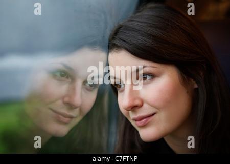 Junge Frau blickte aus dem Fenster auf eine Zugfahrt - Stockfoto