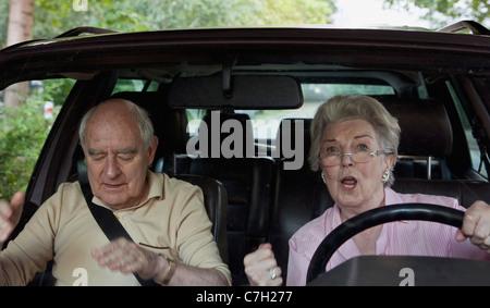 Frau fahren lernen aufgeregt während Mann in Beifahrer Sitz spricht für Ruhe - Stockfoto