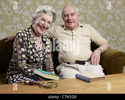 Ältere Mann und Frau mit Buch auf der couch - Stockfoto