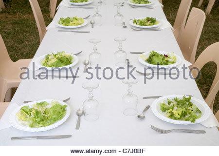 Tisch mit Teller und Besteck mit grünem Salat - Stockfoto