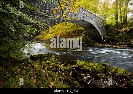Stein-Steg über einen kleinen Fluss im Herbst, Lake District, England, UK - Stockfoto