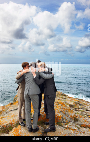 Geschäftsleute im Huddle auf Klippe sprechen - Stockfoto