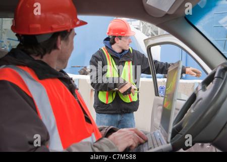 Arbeiten am Laptop in einem LKW und Erteilung von Anweisungen an ein anderer Ingenieur Ingenieur - Stockfoto