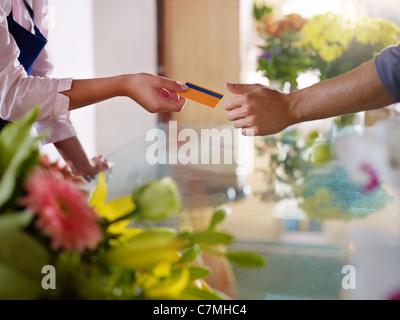 Junge Frau arbeitet als Florist Kreditkarte Kunden zu geben nach dem Kauf. Horizontale Form, Nahaufnahme - Stockfoto