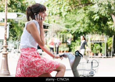 Frau, Fahrrad fahren und telefonieren mit einem Handy, Paris, Ile de France, Frankreich - Stockfoto