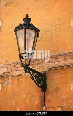 Schmiedeeisen Laterne mit seinen Schatten auf die gelbe Wand, Prag, Tschechische Republik - Stockfoto