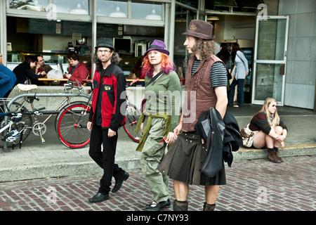 Mädchen mit orange Haare & lila Hut auf dem Pike Place, begleitet von 2 langhaarigen Jungen Männer eine trägt einen - Stockfoto