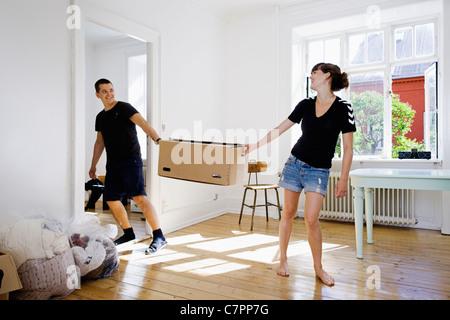 Paar mit Box im neuen Zuhause - Stockfoto