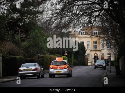 BSM Instruktoren Steuerwagen rundet einen stationäre Mercedes in einem in der Regel Vorort Straße in England UK - Stockfoto