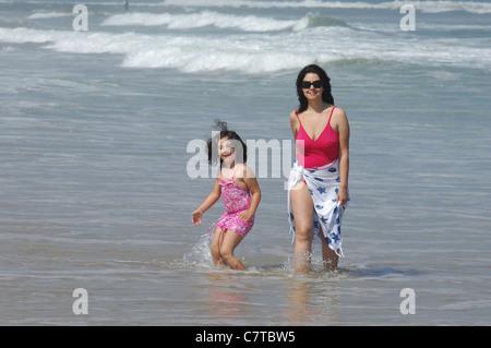 Mutter und Kind am Strand in der Nähe von Wasser am Strand - Stockfoto