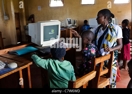 Ein Lehrer, Kindern zu helfen, während einer einleitenden Computerklasse, Meserani, Tansania. - Stockfoto