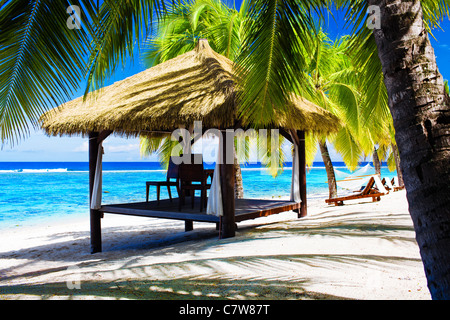 Tropischen Pavillon mit Stühlen am einsamen Strand mit Palmen - Stockfoto