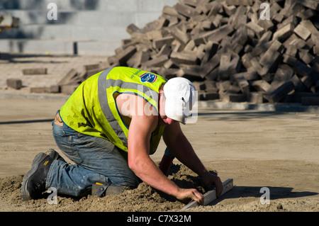 Ein Arbeiter verlegen neue Pflastersteine auf einer Baustelle in einem Zeitraum von heißem Wetter - Stockfoto