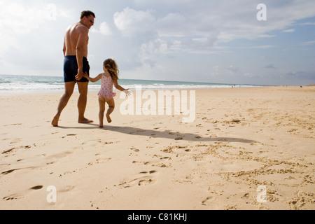 Vater & Tochter am Strand entlang spazieren Hand in Hand, im Urlaub am Strand - Stockfoto
