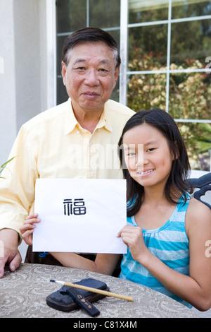 Chinesischen Großvater Lehre Enkelin Kalligraphie - Stockfoto