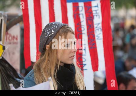 """Ein Demonstrant vor einer amerikanischen Flagge mit den Worten """"Die neue amerikanische Revolution"""" während Demonstration - Stockfoto"""