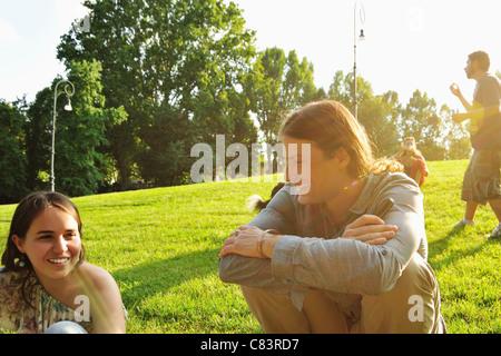 Freunde sitzen in Rasen im park - Stockfoto
