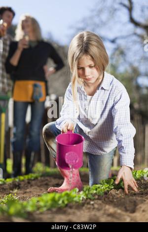 Mädchen Bewässerung von Pflanzen im Garten - Stockfoto