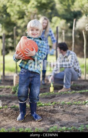 Jungen tragen Kürbis im Garten - Stockfoto