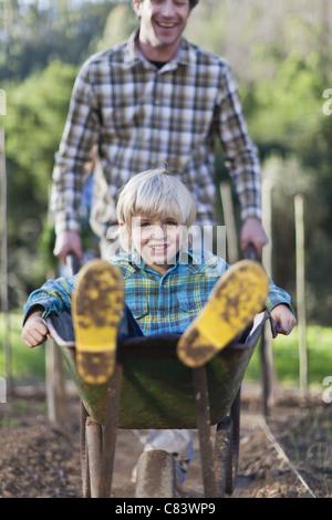 Vater drängt Sohn in Schubkarre - Stockfoto