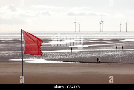 Rote Fahne warnt Schwimmer wie Windräder im Ozean vor einem Sandstrand in der Nähe von Liverpool an einem kalten - Stockfoto