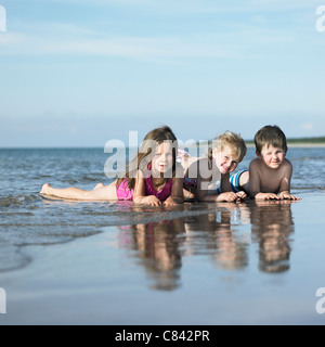 Kinder spielen in den Wellen am Strand - Stockfoto