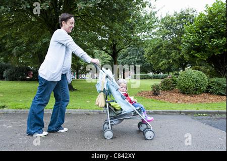 Mutter drängt Tochter im Kinderwagen - Stockfoto