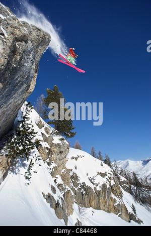 Skifahrer in der Luft auf verschneiten Bergen - Stockfoto