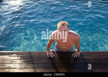 Mann aus Schwimmbad Klettern - Stockfoto