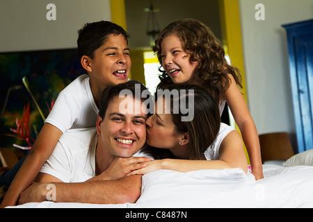 Lächelnd hispanischen Familie mit auf Bett zusammen - Stockfoto