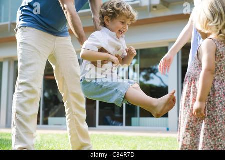 Kleiner Junge mit seiner Familie im Freien zu spielen - Stockfoto