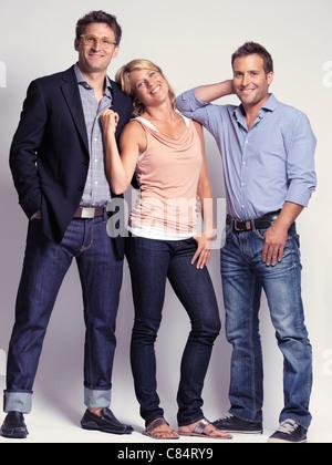 Lächelnd gekleidet, lässig, aber mit Stil, zwei Männer und eine Frau in jeans - Stockfoto