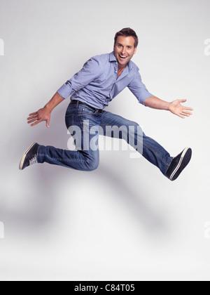 Glücklich springen jungen Mann trägt Jeans und ein Hemd auf grauem Hintergrund isoliert - Stockfoto
