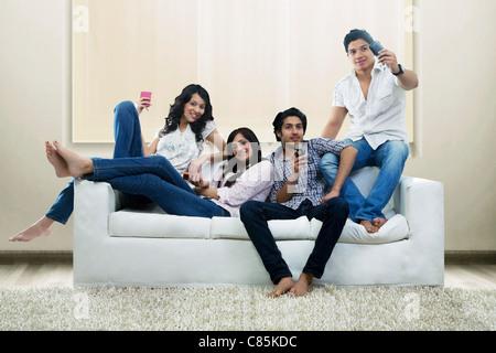 Jugendlichen mit Handys, die auf einem Sofa sitzt - Stockfoto