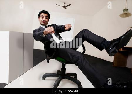 Geschäftsmann, die vorgibt, im Büro Motorradrennfahrer - Stockfoto