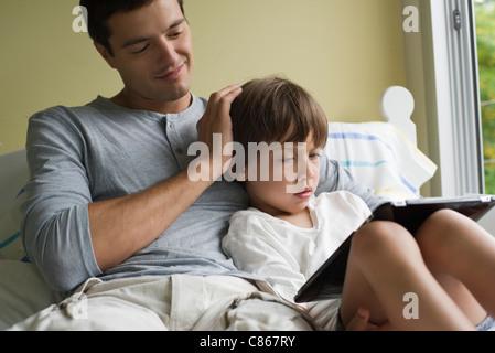 Vater und Sohn zusammen mit elektronischen Buch entspannende - Stockfoto