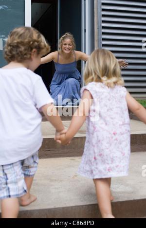 Junge Geschwister Hand in Hand, laufen in Richtung Mutter - Stockfoto