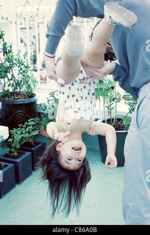 Vater hält kleine Mädchen auf den Kopf gestellt - Stockfoto