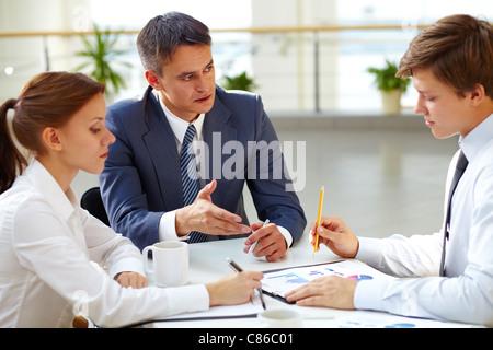 Junge Büroangestellte, die Berichterstattung zu seinem Chef über Arbeit - Stockfoto