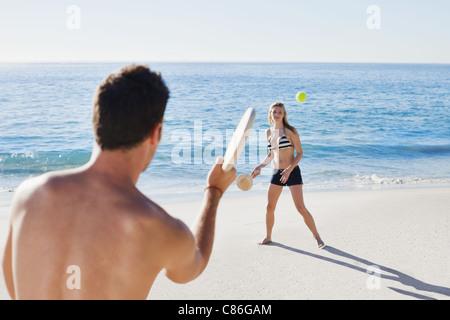 Paar am Strand Tennis spielen - Stockfoto