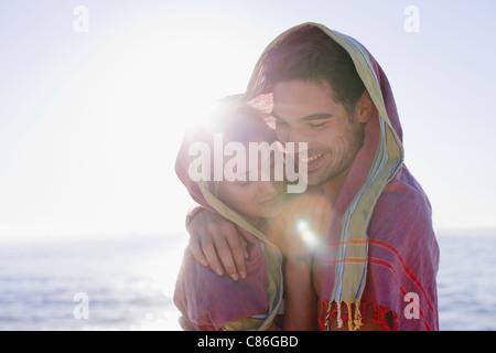 Paar umarmt unter Decke am Strand - Stockfoto
